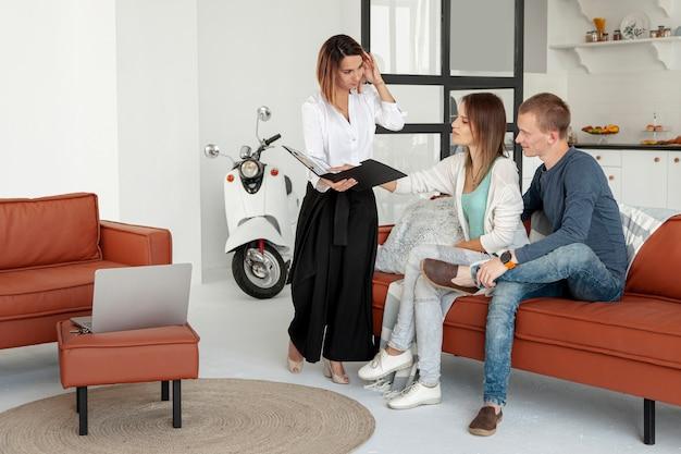 Agente imobiliário falando com homem e mulher