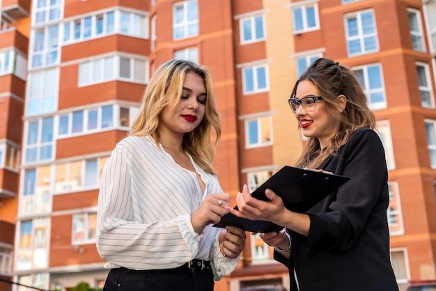 Agente imobiliário feminino com chave da área de transferência e cliente jovem perto da casa à venda ao ar livre