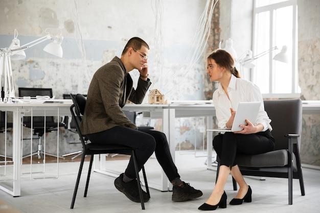 Agente imobiliário feminino mostrando a nova casa para um jovem após uma discussão sobre os planos da casa.