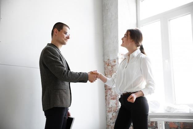 Agente imobiliário feminino mostrando a nova casa para um jovem depois de uma discussão sobre os planos da casa, movendo-se, novo conceito de casa