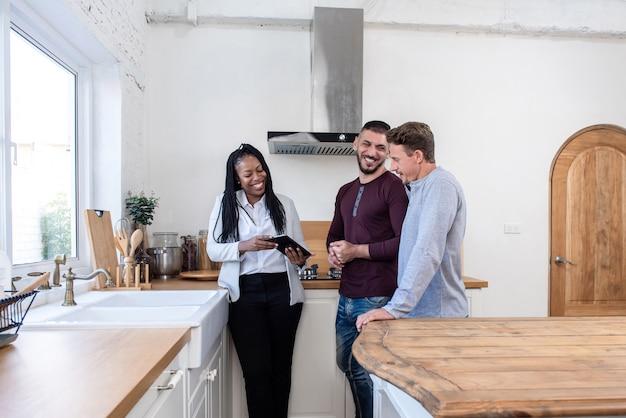 Agente imobiliário feminino mostrando casal gay em torno de casa nova