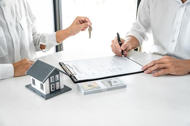 Agente imobiliário gerente de vendas com chaves de arquivo para o cliente após a assinatura do contrato de locação