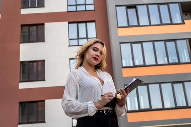Agente imobiliário jovem atraente que segurando as chaves em pé contra a nova casa moderna ao ar livre. conceito de venda