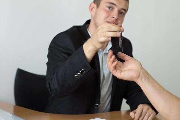 Agente imobiliário masculino jovem dando a chave da casa para o comprador enquanto olha para a câmera.