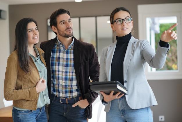 Agente imobiliário mostrando casa moderna para casal atraente
