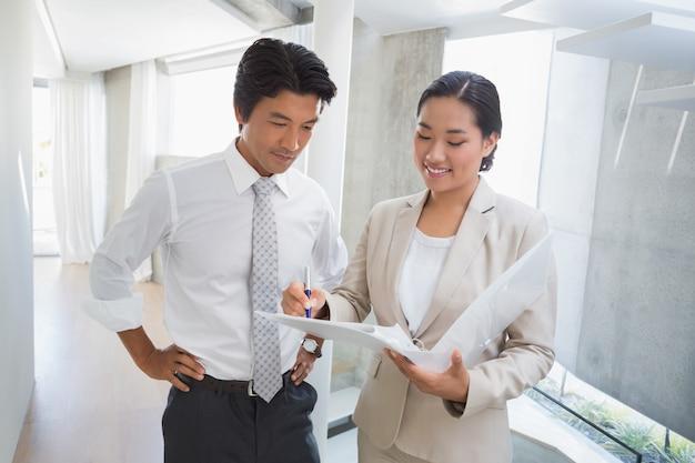 Agente imobiliário mostrando locação ao cliente e sorrindo