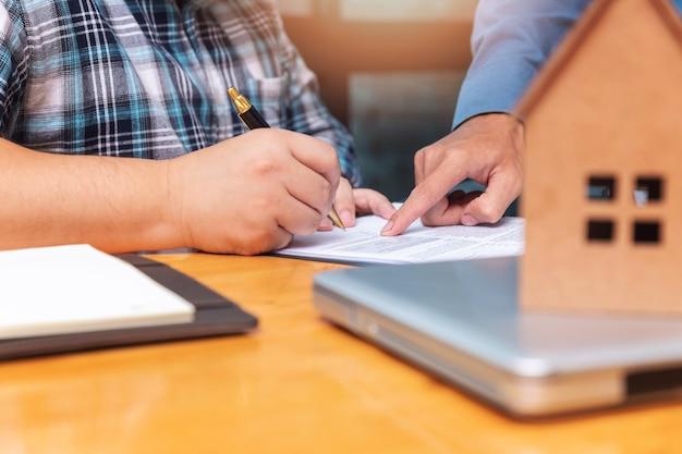 Agente imobiliário mostrando seu cliente onde ele tem que assinar um contrato de acordo de vedação.