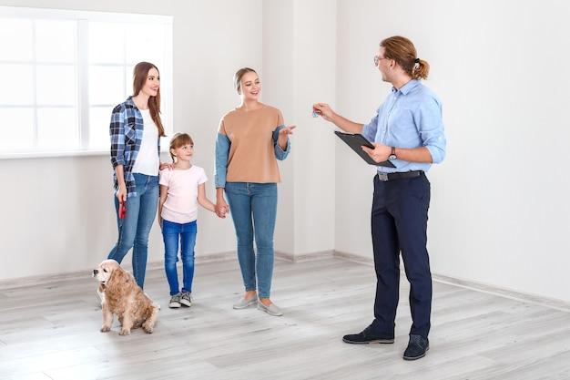 Agente imobiliário mostrando uma nova casa para uma família lésbica