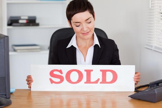 Agente imobiliário olhando para um painel vendido