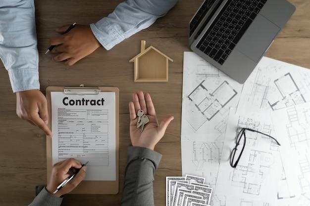 Agente imobiliário que assina um contrato sobre uma casa empréstimo imobiliário chave