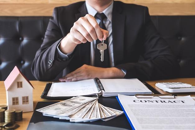 Agente imobiliário que dá as chaves da casa ao cliente após ter assinado a propriedade do contrato do acordo com aprovado