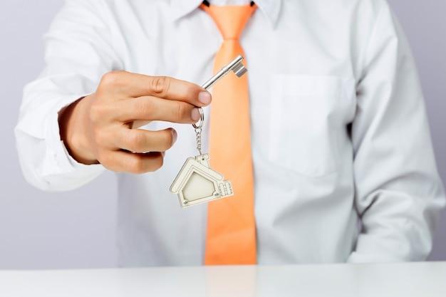 Agente imobiliário que dá chaves da casa, fundo isolado,