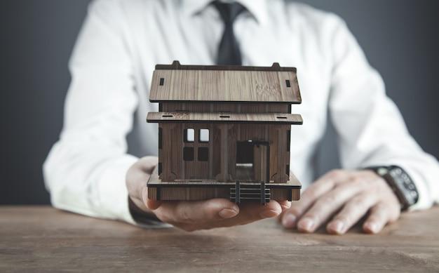 Agente imobiliário segurando a casa de madeira.