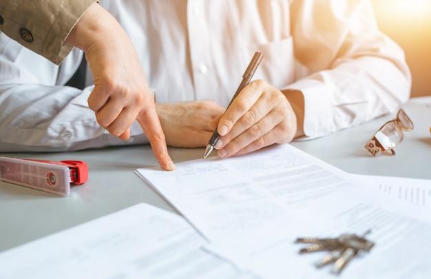 Agente imobiliário segurando a chave da casa para seu cliente após a assinatura do contrato. conceito de imóveis, negócios e propriedades
