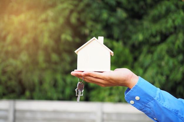 Agente imobiliário segurando as chaves e casa em miniatura