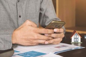 Agente imobiliário trabalhando com telefone inteligente e documento na mesa de madeira no escritório