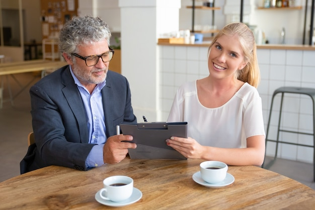 Agente jovem e cliente maduro se encontrando para tomar uma xícara de café em um colega de trabalho, sentado à mesa, segurando documentos,