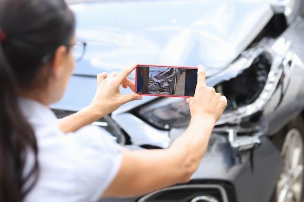 Agente mulher tira fotos de danos ao carro após acidente devido às consequências do carro no smartphone