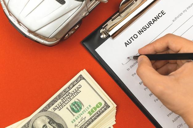 Agente preenchendo formulário de seguro de carro. área de transferência com acordo e política, dinheiro e brinquedo de carro na área de trabalho de escritório do agente. fundo vermelho e foto da vista superior