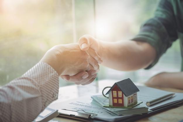 Agentes imobiliários concordam em comprar uma casa e dar chaves aos clientes nos escritórios da agência.