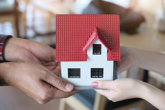Agentes imobiliários que dão casas aos clientes. conceitos de imóveis e terrenos.