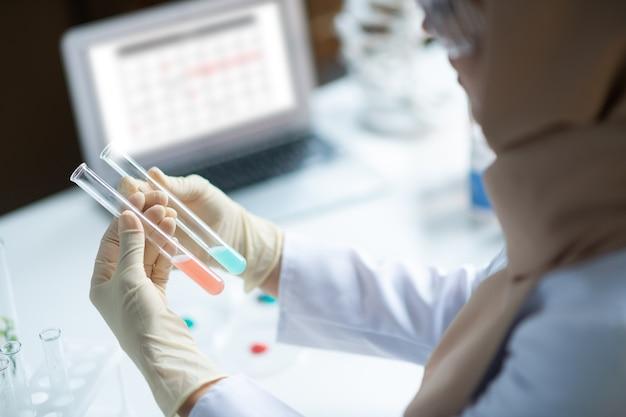 Agentes químicos coloridos. química feminina de uniforme sentada perto de um laptop e estudando agentes químicos coloridos