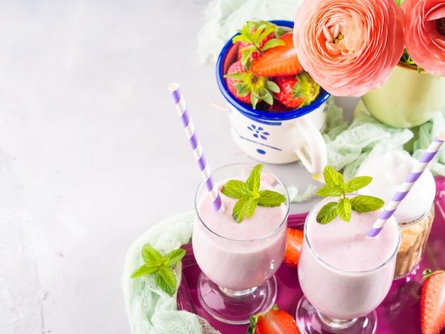 Agitação de leite da morango nos vidros para o café da manhã romântico. configuração de mesa de verão com flores de ranúnculo