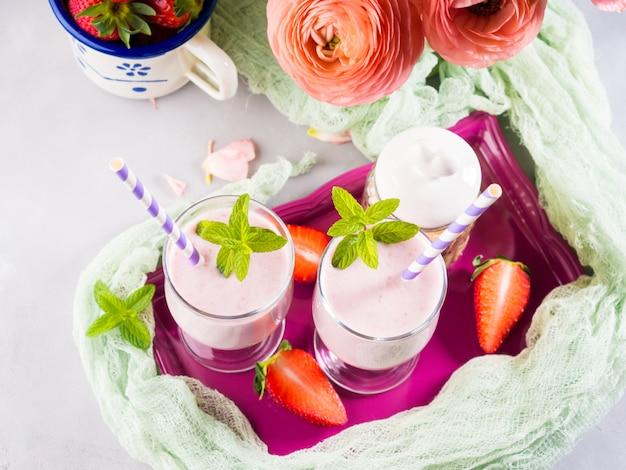 Agitação de leite da morango nos vidros para o café da manhã saudável do verão romântico. configuração de mesa de verão com flores de ranúnculo