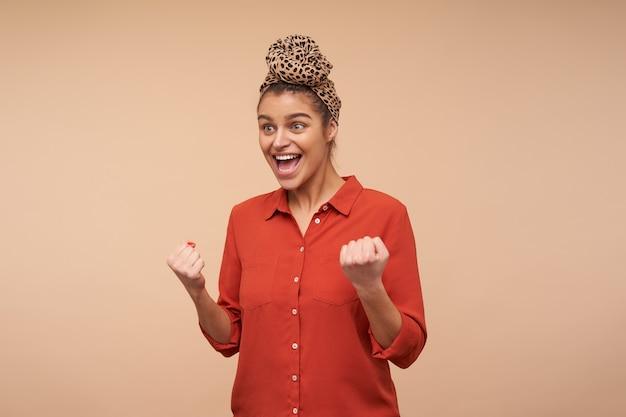 Agitada jovem senhora de cabelos castanhos usando uma faixa na cabeça com um nó enquanto posava sobre uma parede bege, levantando animadamente as mãos e gritando feliz com a boca aberta Foto gratuita