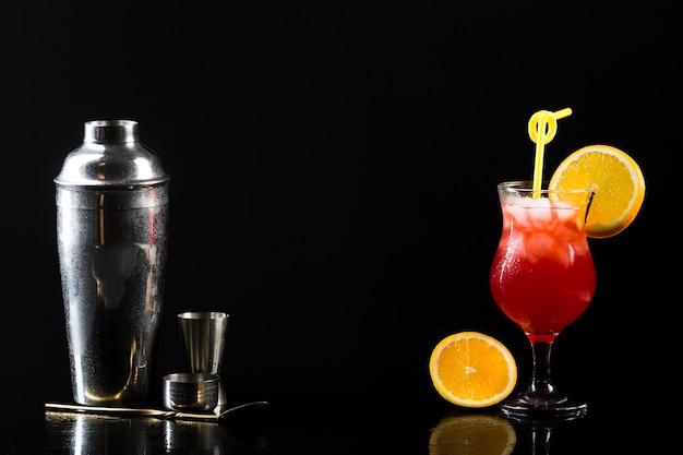 Agitador e copo de coquetel com laranja e copie o espaço