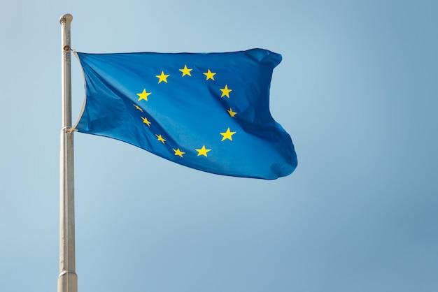 Agitando a bandeira da ue da união europeia no fundo do céu azul
