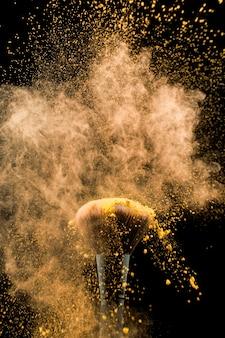 Agitando a escova cosmética em pó amarelo