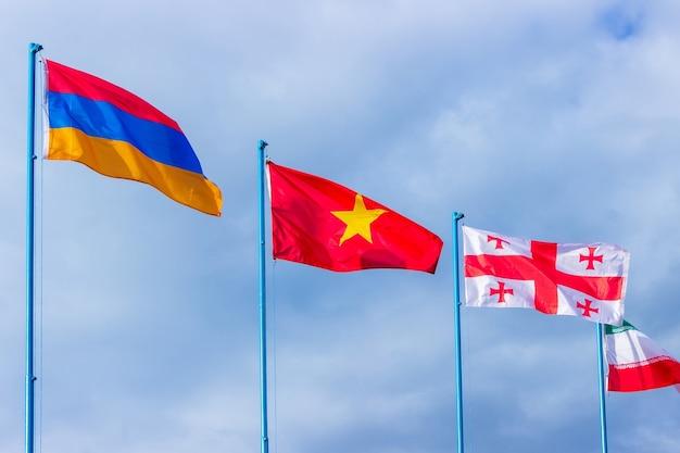 Agitando bandeiras da armênia, china, geórgia e irã no céu azul. amizade de países e povos