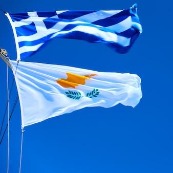 Agitando bandeiras gregas e cipriotas contra o céu azul com vento forte
