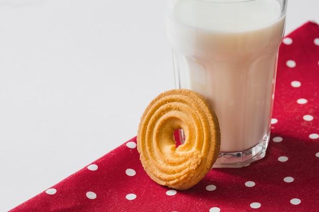 Agite o biscoito patter perto do copo de leite no guardanapo vermelho sobre o fundo branco