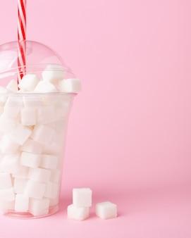 Agite o copo cheio de cubos de açúcar no fundo rosa conceito de ingestão excessiva de açúcar