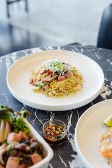 Agite o macarronete chinês fritado com carne do presunto e de caranguejo na tabela superior de mármore preta.