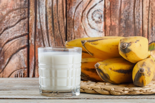 Aglomerado de bananas com vista lateral do leite em uma mesa de madeira e vime
