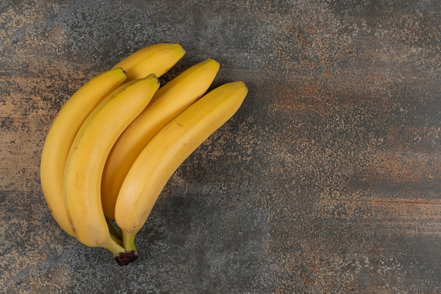 Aglomerado de bananas maduras na mesa de mármore.