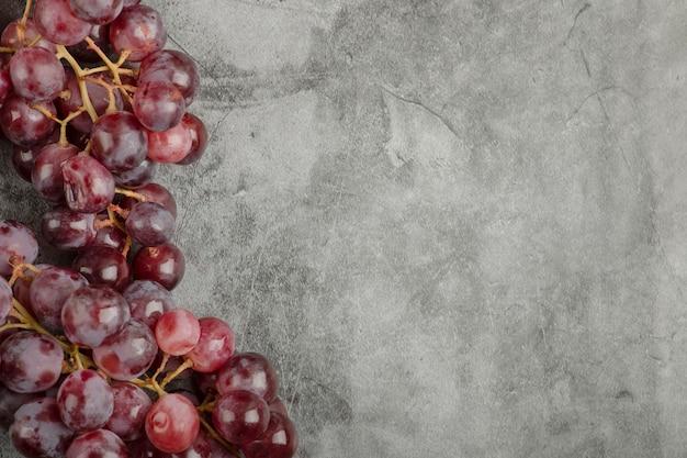 Aglomerado de uvas maduras frescas vermelhas na superfície de mármore.
