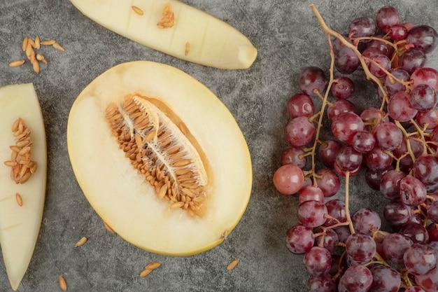 Aglomerado de uvas vermelhas maduras e melão fatiado na superfície de mármore.