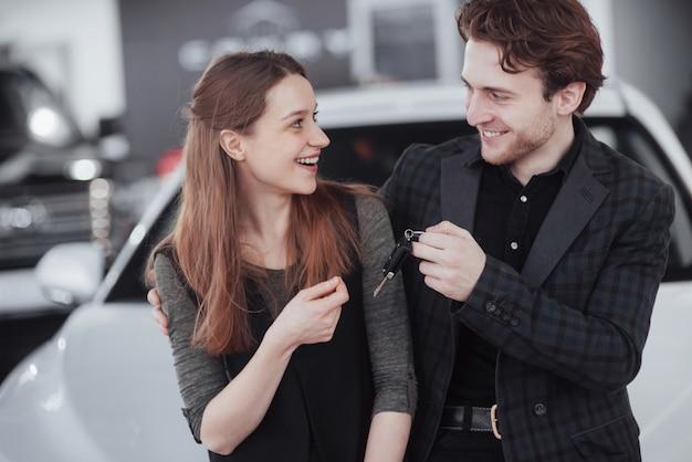 Agora o sonho dela se torna realidade. vendedor de carros, dando a chave do carro novo aos jovens proprietários atraentes