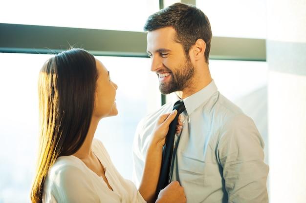 Agora você está pronto! jovem casal apaixonado, cara a cara, sorrindo enquanto a mulher ajeita a gravata do marido