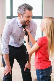 Agora você está pronto para ir. menina brincalhona ajudando o pai a amarrar uma gravata