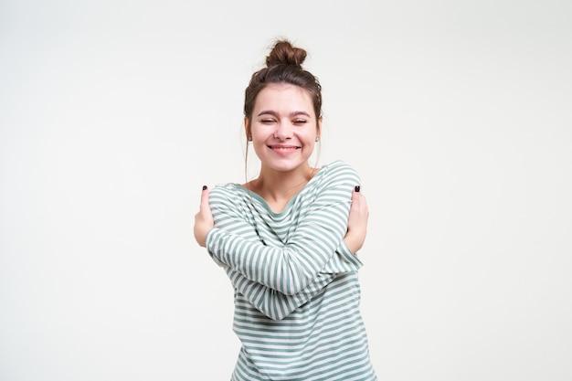 Agradada, jovem adorável senhora de cabelos castanhos mantendo os olhos fechados enquanto se abraçava e sorria agradavelmente, em pé sobre uma parede branca com uma blusa listrada