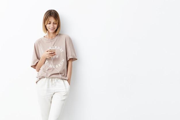 Agradável aparência feminina com penteado da moda, mantendo a mão no bolso, usando o celular para comunicação com amigos ou amante, ouvindo música agradável, tendo bom humor no início da manhã