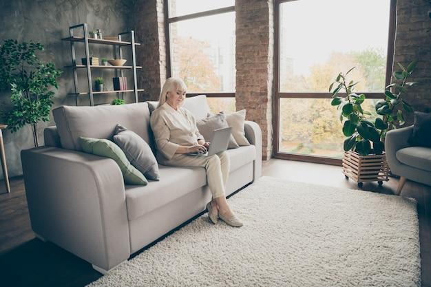 Agradável, atraente, calmo, tranquilo, focado, tipo, qualificada senhora de cabelos grisalhos, sentada no divã, navegando informações online, consulta médica, visite loft de tijolos industriais estilo moderno interior casa sala de estar
