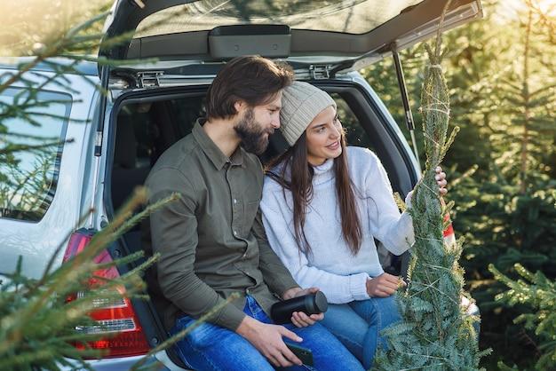 Agradável casal sentado no porta-malas do carro olhando a maravilhosa árvore de natal que escolheram