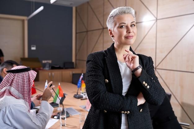 Agradável empresária com cabelo curto e roupa formal, posando na sala de reuniões durante reunião com um grupo internacional de políticos sentados à mesa