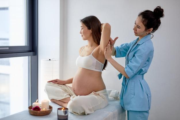 Agradável fisioterapeuta feminina massageando as costas e os ombros da mulher grávida, sentada na cama no gabinete brilhante do spa, com velas. a futura mamãe adulta está gostando de receber massagem